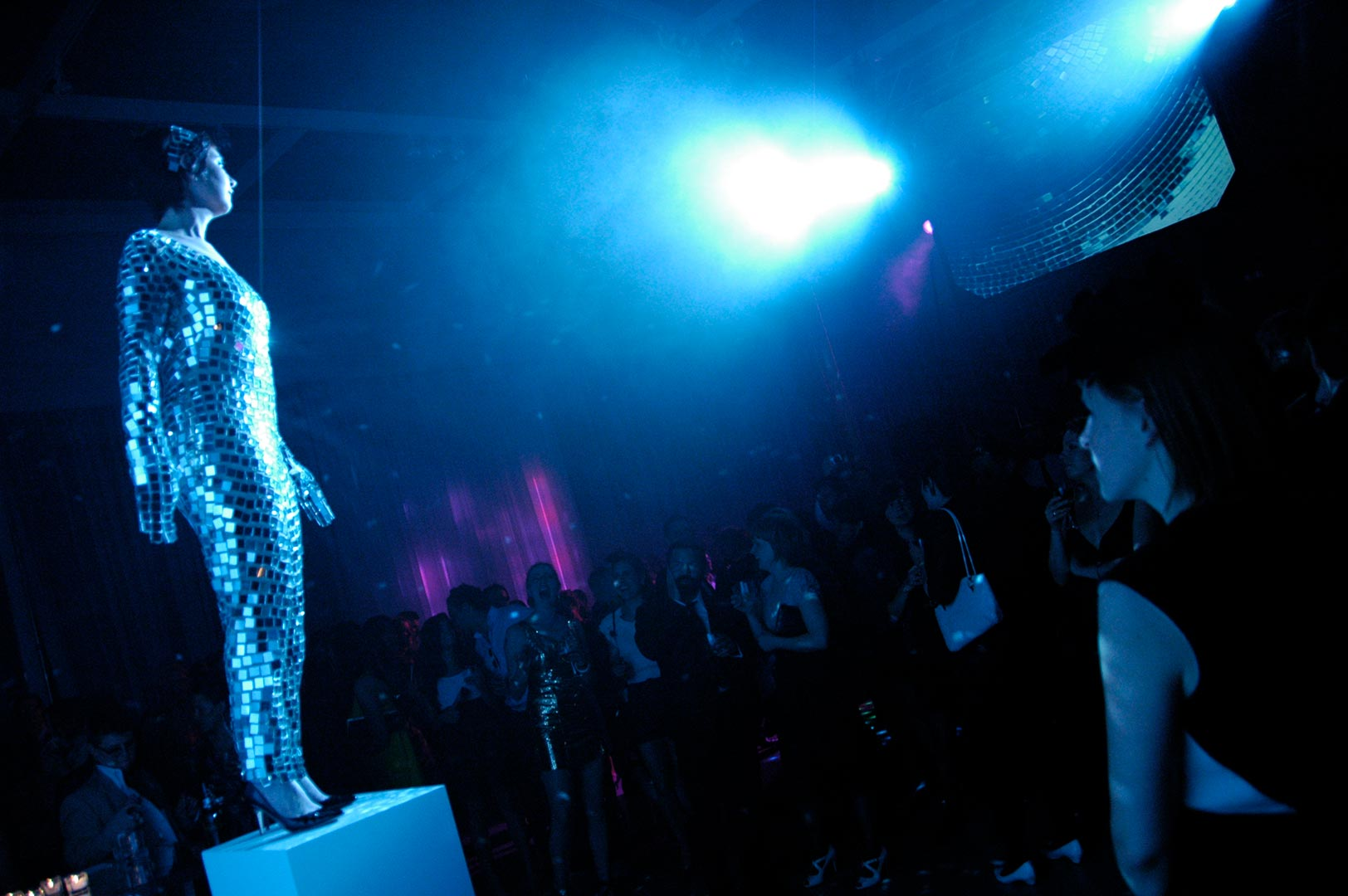 A woman, dressed in a pantsuit resembling a disco ball, stands on a plinth. Spotlit, she is performing for an audience in a darkened environment.